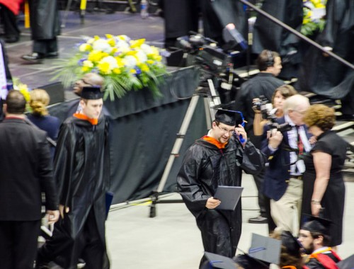 Jared adjusts his tassle after receiving his diploma folder.